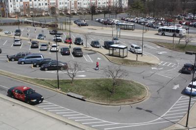 A view of a parking lot, with an old lady carrying bags across.
